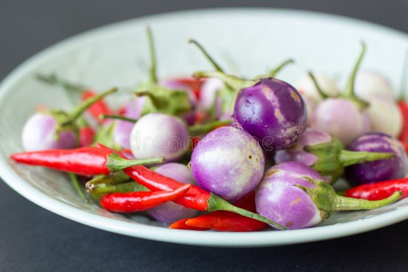 Grüne Platte mit purpurroten thailändischen Auberginen und Pfeffern des scharfen Paprikas auf einem schwarzen Hintergrund Nahaufn stockfotos