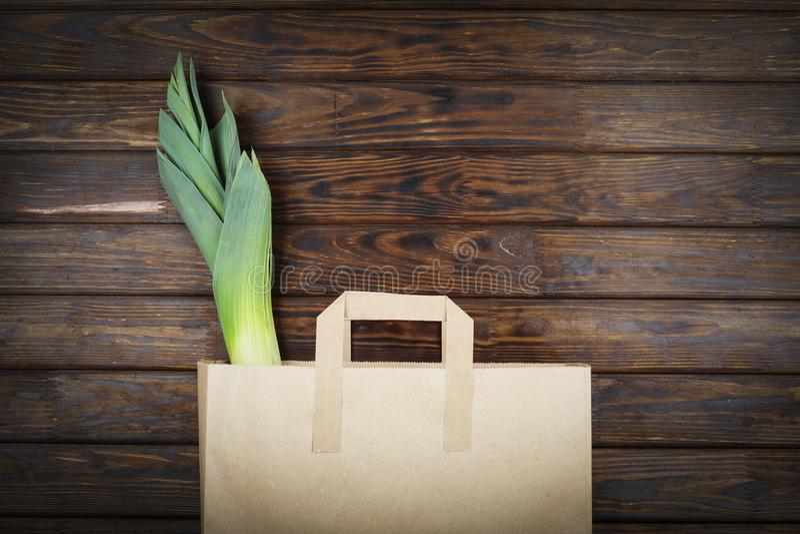 Grüne Produkte, gesundes Lebensmittel, Porree, Vegetarier, Papiertüte, Supermarkt, Lebensmittellieferung, Draufsicht, Kopienraum lizenzfreies stockbild