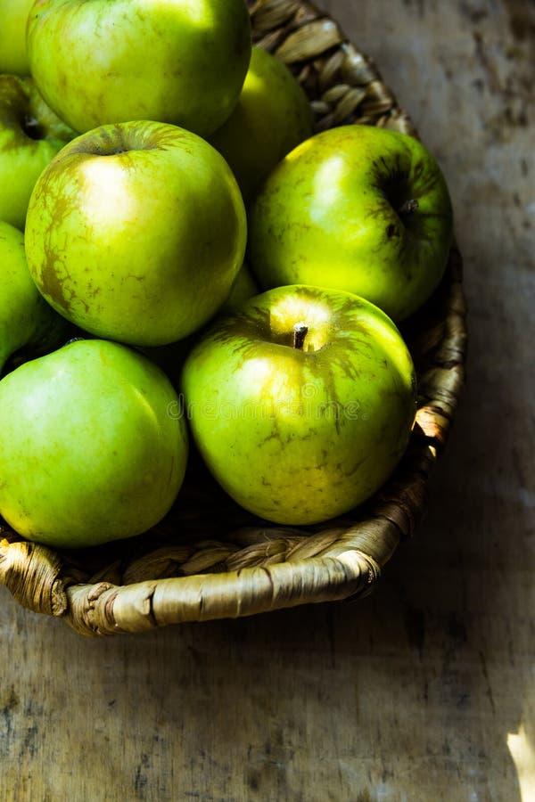 Grüne reife organische Bioäpfel, lokales Erzeugnis, im rustikalen Weidenkorb auf verwitterter hölzerner Tabelle, Ernte lizenzfreies stockfoto