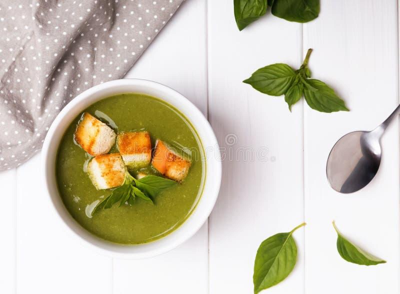 Grüne Sahnesuppe auf der weißen Tabelle stockfotos