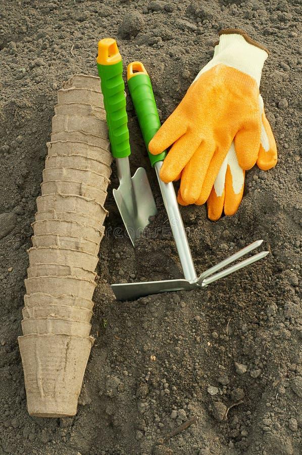 Grüne Schaufelrührstange, Gartenhandschuhe und Torftöpfe für Sämlinge stockfotos