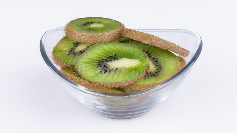 Grüne Scheiben der Kiwi in der ovalen Glasschüssel Fuzzy Kiwifruit Actinidia deliciosa lizenzfreie stockfotos