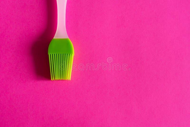 Grüne Silikonbürste mit weißem Griff auf rosa Hintergrund stockfotografie