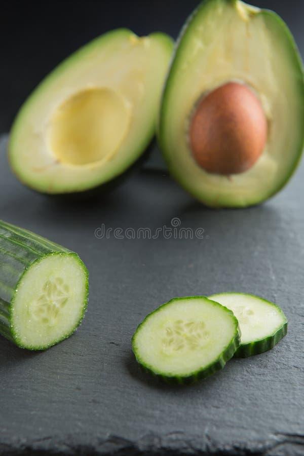Grüne Smoothiebestandteile - Avocado, Gurke auf einem dunklen Hintergrund stockbilder