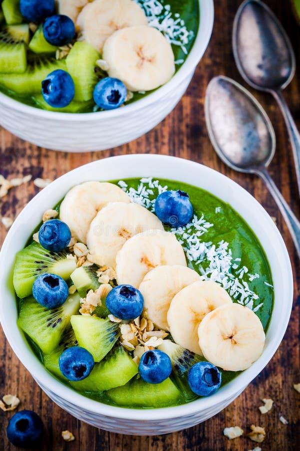 Grüne Smoothieschüssel mit Banane, Kiwi, Blaubeere, Granola und Kokosnuss stockfotografie