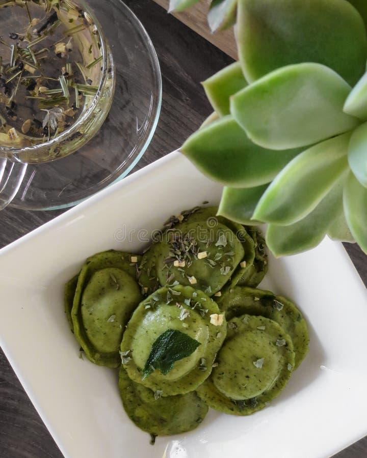 Grüne Spinatsravioli und Kräutertee lizenzfreie stockfotografie