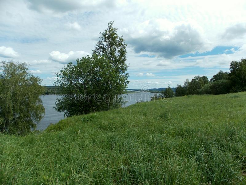 Grüne Steigung über dem Fluss lizenzfreie stockfotos
