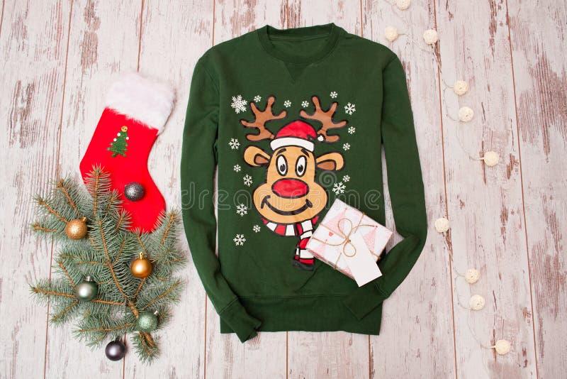 Grüne Strickjacke mit einem Ren auf einem hölzernen Hintergrund Pelz-Baumniederlassung mit Weihnachtsdekorationen, Zitrusfrucht lizenzfreies stockfoto
