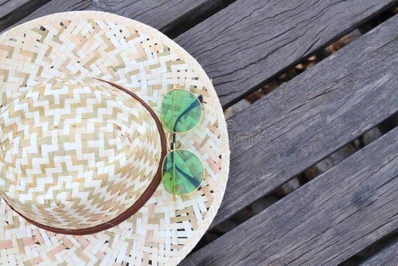 grüne sunglass und Hut auf einem hölzernen Brückenhintergrund lizenzfreie stockfotos