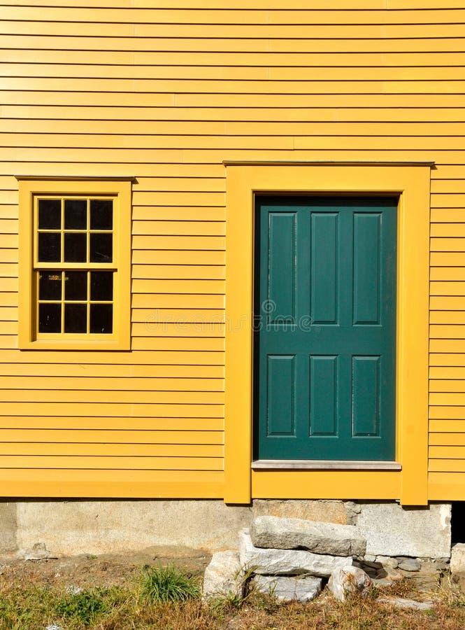 Grüne Tür auf gelber Außenwand mit Fenster lizenzfreie stockfotos