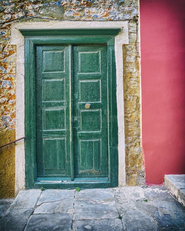 Grüne Tür der Weinlese auf Steinwandhaus mit dunklem rosa Teil lizenzfreie stockfotografie