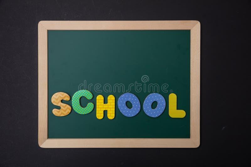 Grüne Tafel mit Holzrahmen, Wortschule in den bunten Buchstaben, schwarzer Wandhintergrund stockbilder