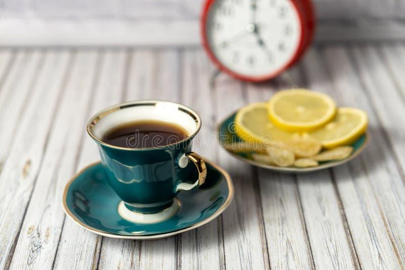 Grüne Tasse heißen Tee, Saucer mit Zitronen und kandierte Ingwer auf einem Holztisch mit rotem Wecker im Hintergrund lizenzfreie stockfotos