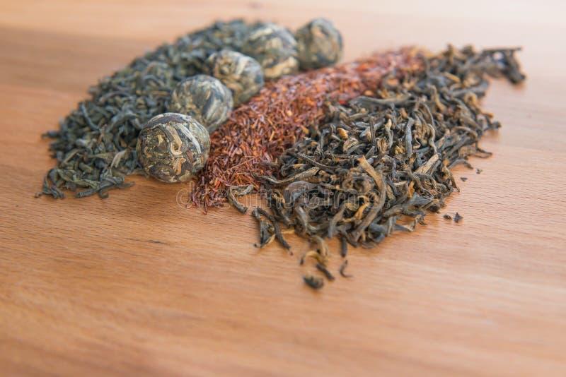 Grüne Teeblätter, puer Bälle, rooibos Blätter und schwarzer Tee auf wo stockbild