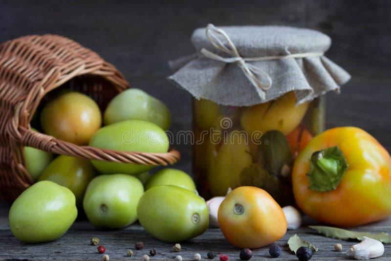 Grüne Tomaten in einem Korb und in Essig eingelegte Tomaten in einem Glas stockfoto