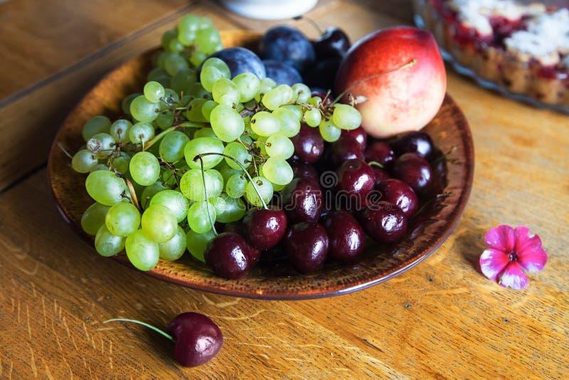 Grüne Traube, Kirsche, Pfirsich, Pflaumen in einer Schüssel stockfotografie
