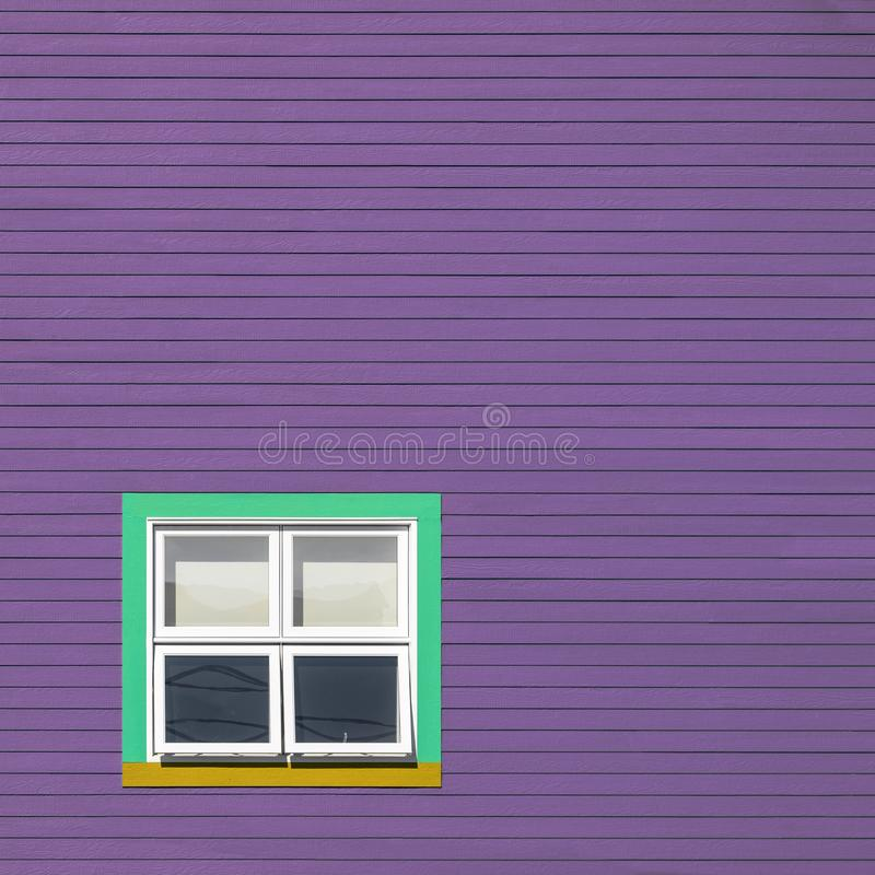 Grüne und gelbe Fenster auf blauer Wand stockbilder