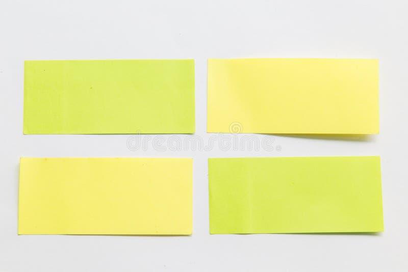 Grüne und gelbe Post-Itpapieranmerkung über weißen Hintergrund lizenzfreie stockfotografie