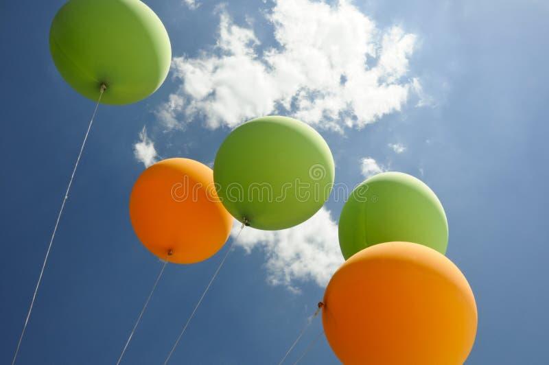Grüne und orange Ballone, die in Richtung zur Sonne fliegen stockfotos