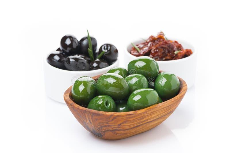 grüne und schwarze Oliven, sonnengetrocknete Tomaten in Schüsseln, lokalisiert stockfotografie