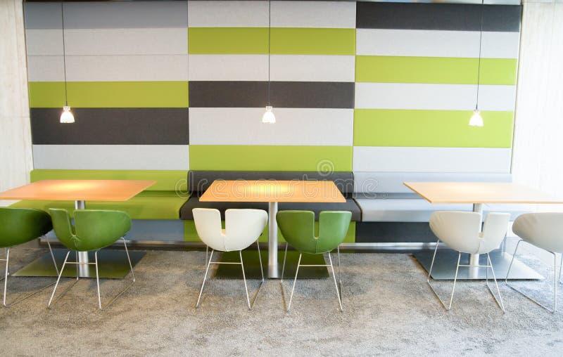 Grüne und weiße Stühle und Tabellen in der modernen Cafeteria stockfoto