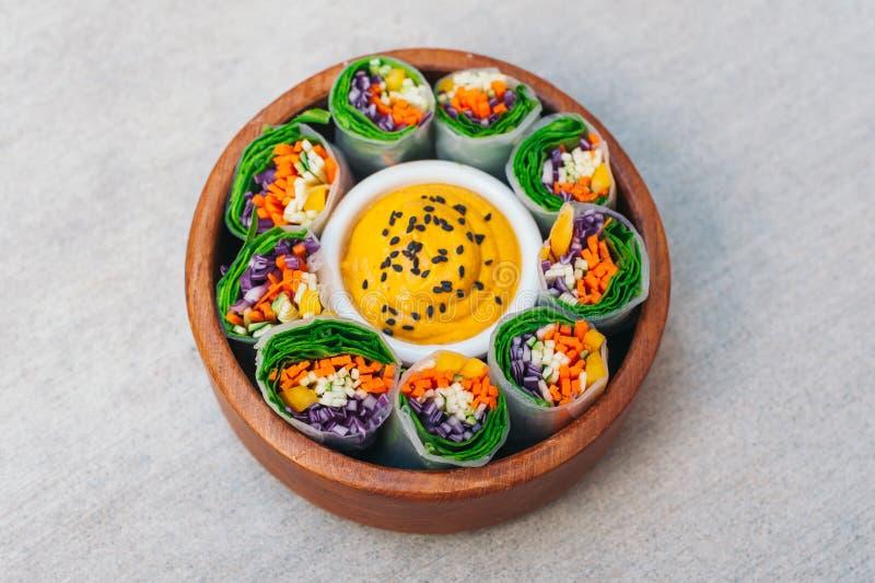 Gr?ne vegetarische Fr?hlingsrollen in der Sch?ssel um Curryso?e Appetitanregende Rollen gef?llt mit der Karotte, Gurke und purpur stockfotografie