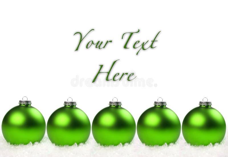 Grüne Weihnachtskugeln richteten im Schnee aus lizenzfreie stockfotografie