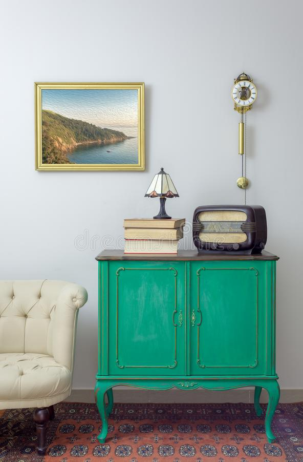 Grüne Weinleseanrichte mit altem Radio und Stapel von alten Büchern und von Tischlampe auf Hintergrund weg von der weißen Wand mi stockfoto