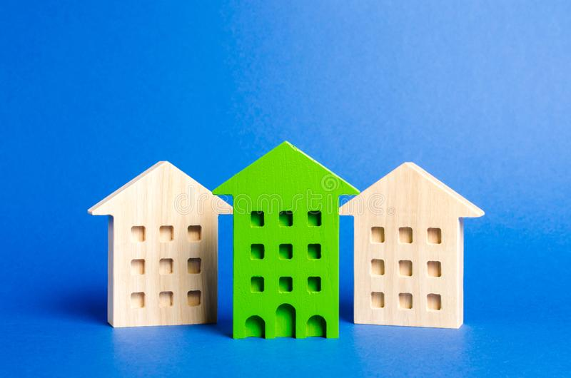 Grüne Zahl eines Wohngebäudes steht heraus unter dem Rest der Häuser Suche nach der besten Kaufoption eine Wohnung lizenzfreie stockfotos