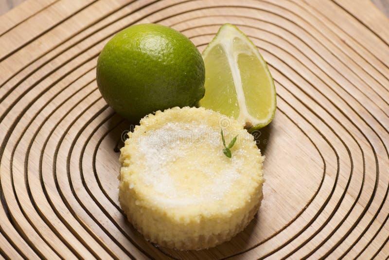 grüne Zitrone scharf und tadellos auf hölzernem Hintergrund lizenzfreie stockfotografie