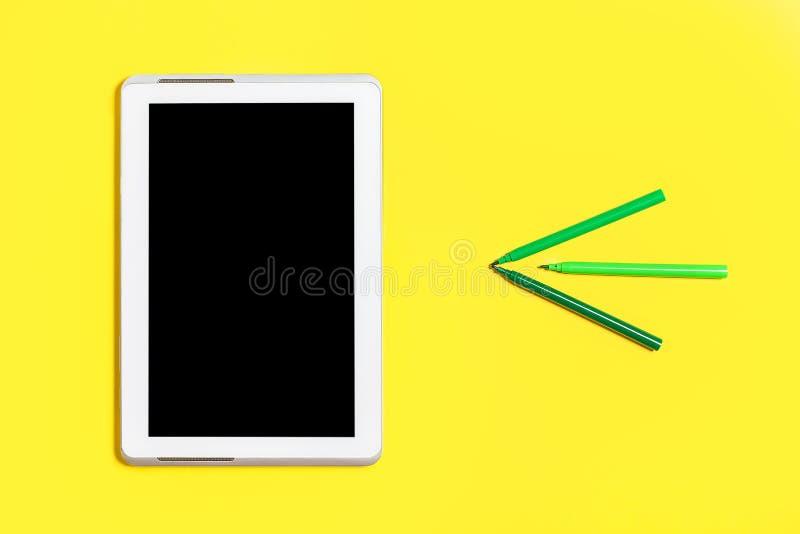 Grünen Sie farbiges Kanzleigericht und einen Tabletten-PC auf einer gelben Oberfläche stockbild