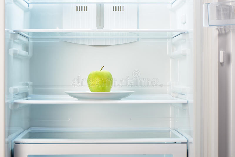 Gruner apfel auf weisser platte im offenen leeren for Grüner kühlschrank