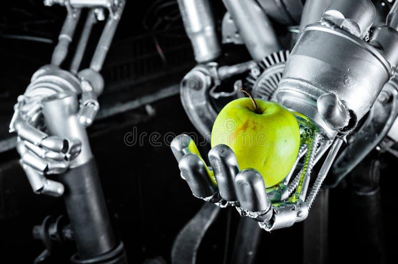 Grüner Apfel in den Händen eines Roboters stockbild