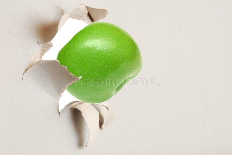 Grüner Apfel durch das heftige Papier lizenzfreie stockfotos