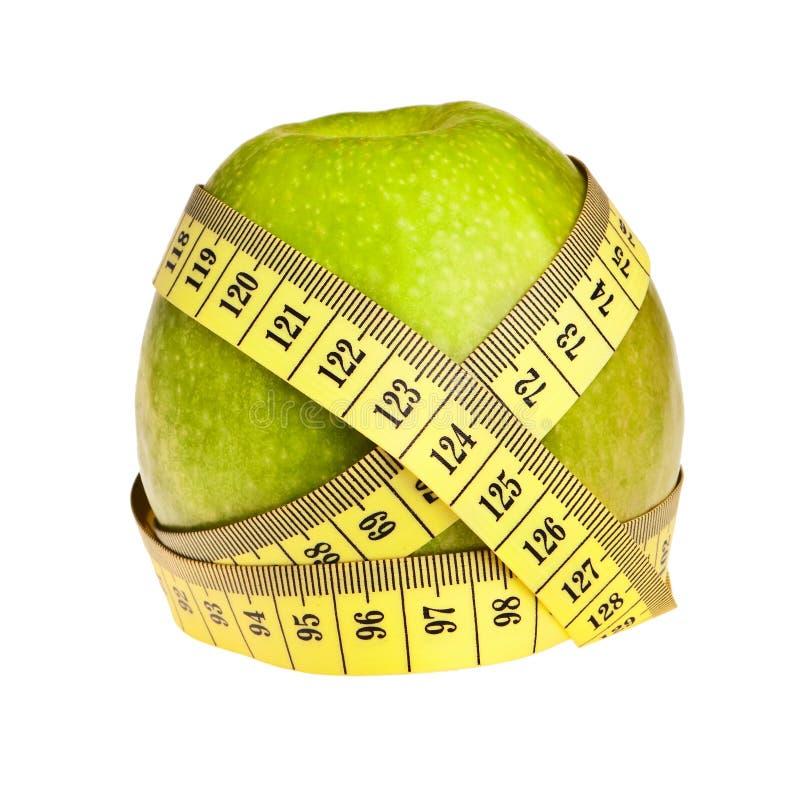 Grüner Apfel eingewickelt mit gelbem Messen-Band. stockbild
