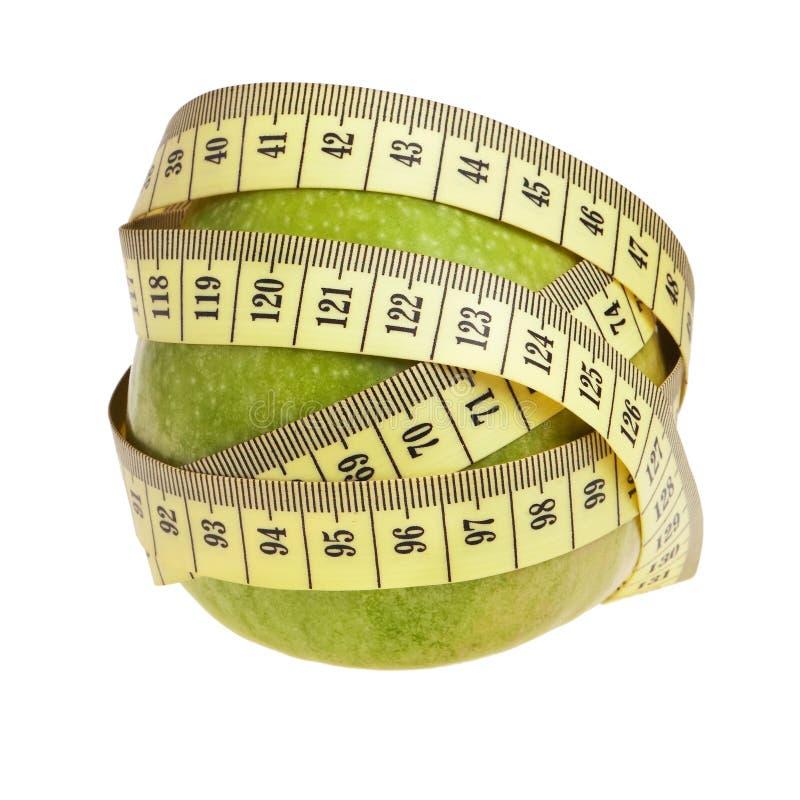 Grüner Apfel eingewickelt mit gelbem Messen-Band. lizenzfreie stockbilder