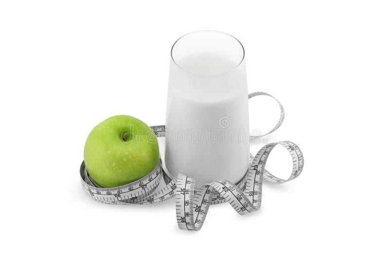 Grüner Apfel, Glas Milch und messendes Band lizenzfreie stockfotografie