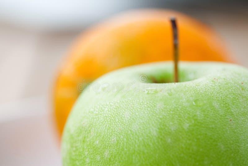 Grüner Apfel mit einer Orange in der Rückseite lizenzfreie stockbilder