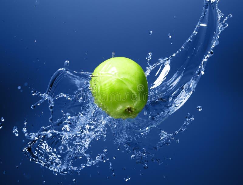 Grüner Apfel mit Wasserspritzen, auf blauem Wasser lizenzfreie stockfotos