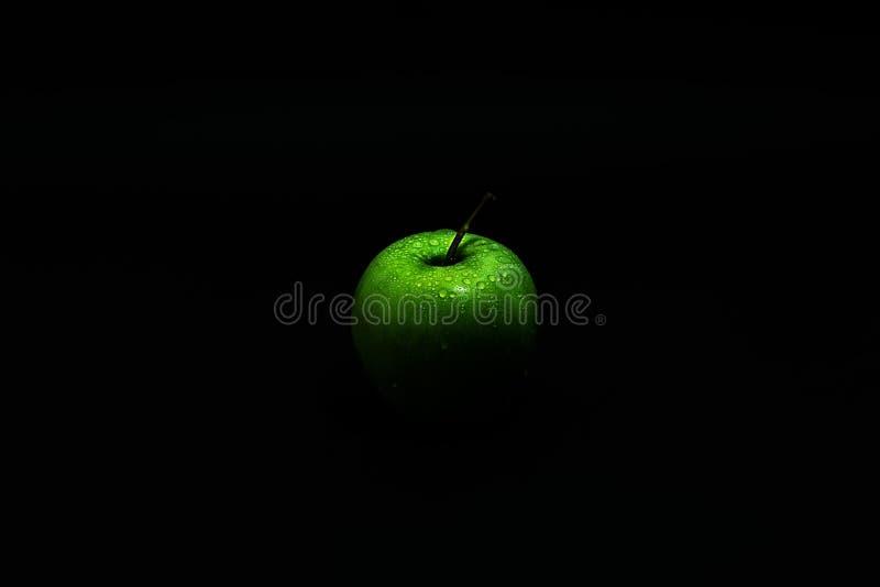 Grüner Apfel mit Wassertropfen auf einem schwarzen Hintergrund stockbild