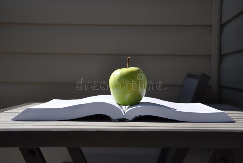 Grüner Apfel und Buch stockfoto