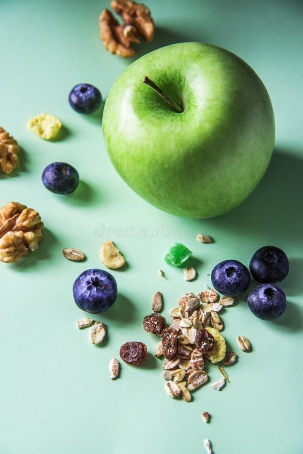 Grüner Apfel und muesli mit Trockenfrüchten und Blaubeeren stockbild