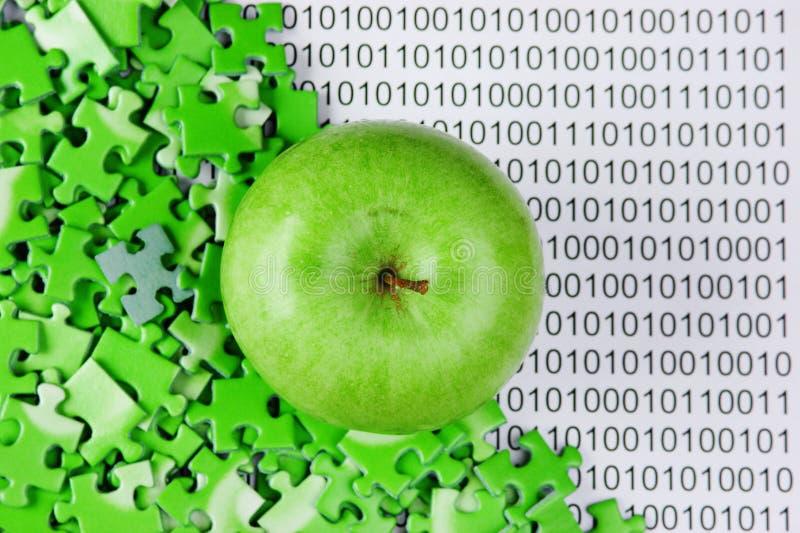 Grüner Apfel und Puzzlespiele auf binär Code stockbild