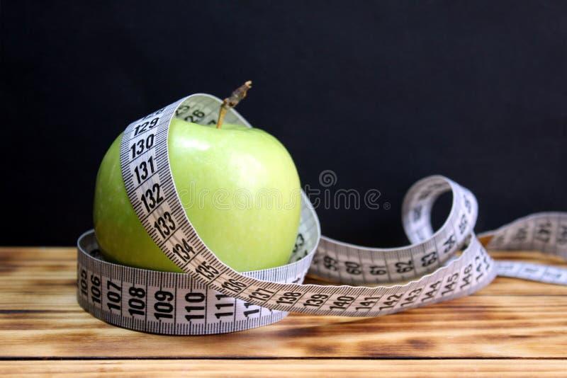 Grüner Apfel verdreht mit einem messenden Band stockfotos