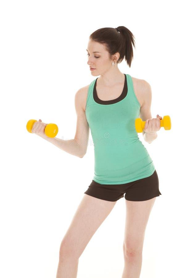 Grüner Behälter der Frau, der gelbe Gewichte hält stockbilder