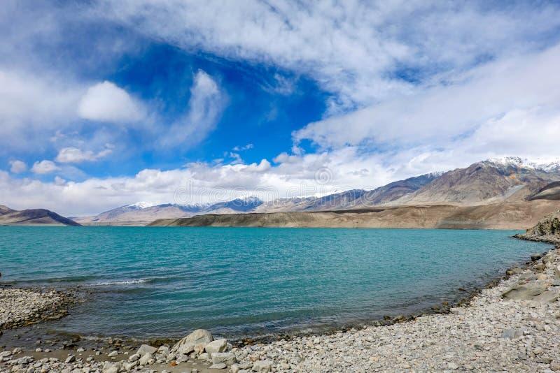 Grüner Besuchssee, Schneeberg, weiße Wolken, blauer Himmel in Pamirrs lizenzfreie stockfotos