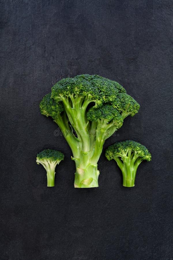 Grüner Brokkoli drei auf dunklem Schieferhintergrund stockbilder