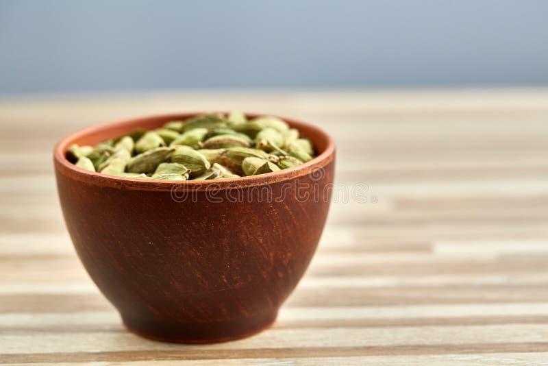 Grüner Cardamon in der keramischen Schüssel auf Holztischnahaufnahme, Draufsicht, selektiver Fokus stockfoto