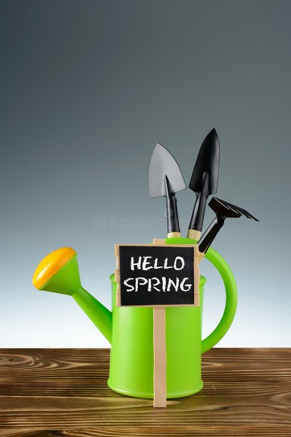Grüner Garten, der mit Werkzeugen und hallo Frühlingszeichen wässert lizenzfreie stockbilder