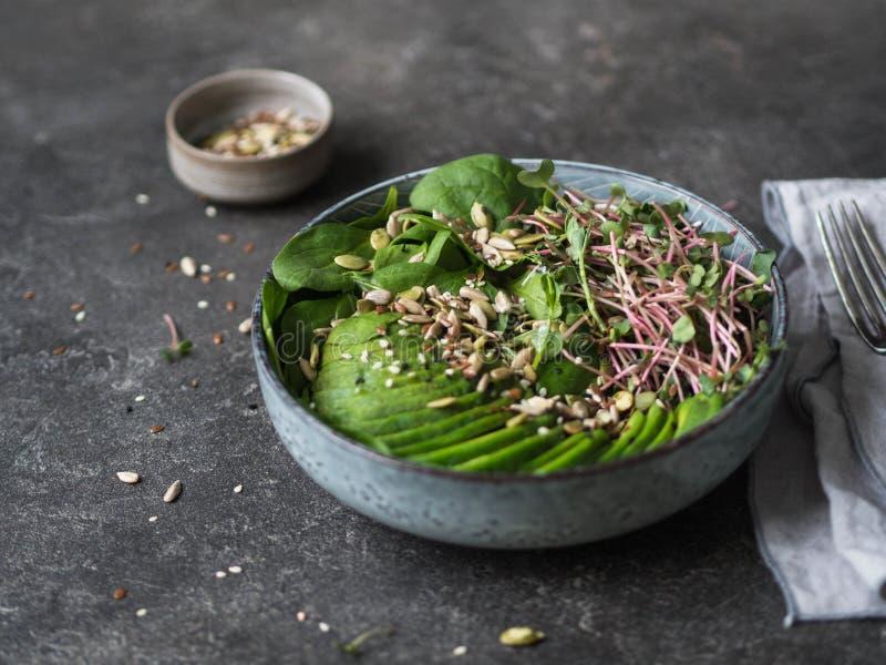 Grüner gesunder Salat des Spinats, der Sprösslinge, der Avocados und der verschiedenen Samen in einer blauen Schüssel auf einem d lizenzfreie stockfotografie